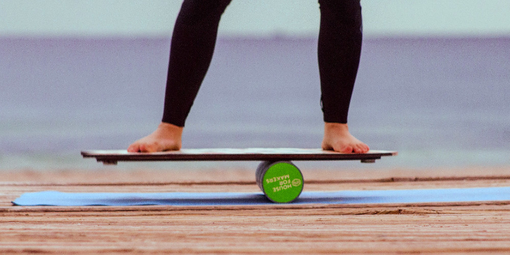 A person balancing on a balance board, as training before surfing.
